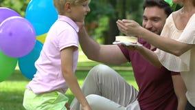 Pais loving que felicitam o rapaz pequeno no aniversário, partido exterior no parque filme