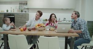 Pais maduros e dois meninos na manhã ao tomar um café da manhã saudável que passam um momento que falam junto video estoque
