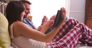 Pais na cama que toma a foto do bebê na tabuleta de Digitas video estoque