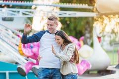 Pais na feira de divertimento, acenando sua criança que toma o passeio Foto de Stock Royalty Free