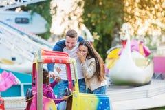 Pais na feira de divertimento, acenando sua criança que toma o passeio Fotografia de Stock Royalty Free