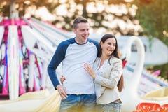 Pais na feira de divertimento, olhando sua criança que toma o passeio Foto de Stock Royalty Free
