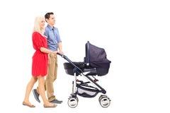 Pais novos que empurram um carrinho de criança de bebê fotografia de stock royalty free