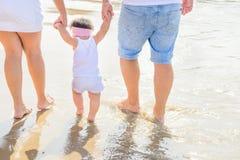 Pais novos que guardam pela filha pequena bonito da menina da criança do bebê das mãos que aprende andar Luz solar do mar da prai foto de stock royalty free