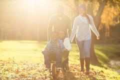 Pais novos que guardam suas crianças em um carrinho de mão Imagem de Stock