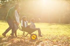 Pais novos que guardam suas crianças em um carrinho de mão Fotografia de Stock Royalty Free