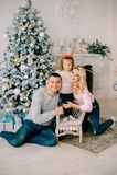 Pais novos que jogam com o bebê perto da árvore de Natal imagem de stock royalty free