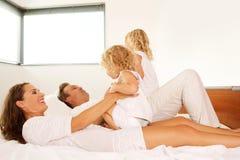 Pais novos que jogam com suas filhas na cama Imagens de Stock