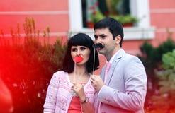 Pais novos que têm o divertimento com o bigode e os bordos feitos do papel Imagem de Stock