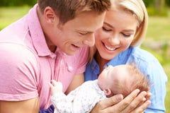 Pais orgulhosos que guardam a filha do bebê no jardim Fotografia de Stock