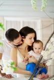 Pais que abraçam e que beijam seu filho do bebê fotografia de stock royalty free