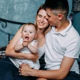 Pais que abraçam a filha do bebê, retrato da família imagem de stock royalty free