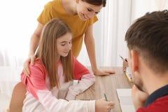 Pais que ajudam sua filha do adolescente com trabalhos de casa foto de stock