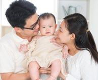 Pais que beijam o bebê Imagem de Stock