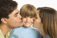 Pais que beijam o filho. imagens de stock