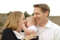 Pais que beijam seu bebê Fotografia de Stock