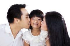 Pais que beijam sua filha imagem de stock royalty free
