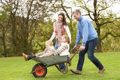 Pais que dão a crianças o passeio no Wheelbarrow fotografia de stock