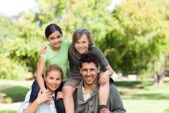 Pais que dão a crianças um sobreposto Imagem de Stock Royalty Free