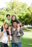 Pais que dão a crianças um sobreposto Imagens de Stock Royalty Free