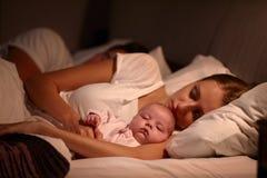 Pais que dormem na cama com bebê recém-nascido Imagens de Stock