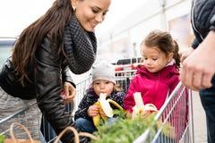 Pais que empurram o carrinho de compras com mantimentos e suas filhas Foto de Stock Royalty Free