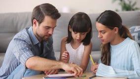 Pais que ensinam a imagem colorindo de fala do desenho da filha da criança com lápis video estoque