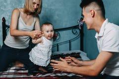Pais que ensinam o bebê pequeno andar em casa cama foto de stock