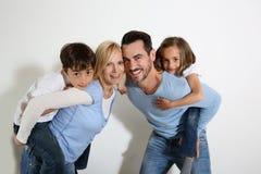 Pais que guardaram crianças em sua parte traseira Fotografia de Stock