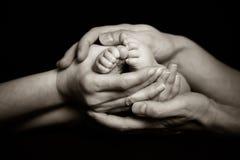 Pais que guardaram os pés da sua criança delicadamente fotos de stock