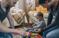 Pais que jogam com criança uma construção de madeira do jogo Foto de Stock