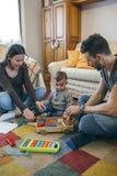 Pais que jogam com criança uma construção de madeira do jogo Fotografia de Stock