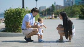 Pais que jogam com seu bebê na aleia video estoque