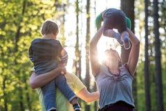 Pais que jogam com suas duas jovens crianças fotografia de stock royalty free
