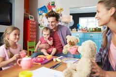 Pais que jogam o jogo com crianças e brinquedos no quarto imagem de stock