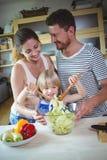 Pais que olham sua filha misturar a salada foto de stock