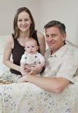 Pais que prendem o bebê Imagem de Stock