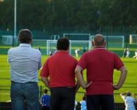 Pais que prestam atenção ao jogo de futebol Fotografia de Stock