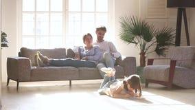Pais que relaxam no sofá quando desenho da filha da criança no assoalho vídeos de arquivo