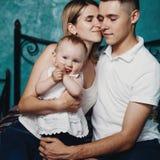 Pais que sentam-se junto abraçando a filha do bebê fotografia de stock