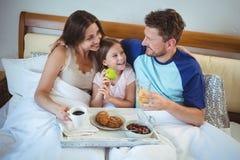 Pais que sentam-se na cama com filha e que comem o café da manhã imagem de stock royalty free