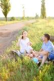 Pais que sentam-se na grama com poucas criança e bolhas de sopro imagens de stock