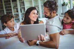 Pais que sentam-se no sofá com suas crianças e que usam a tabuleta digital na sala de visitas foto de stock royalty free
