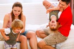 Pais que têm o divertimento com as filhas no sofá fotografia de stock royalty free