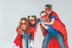 pais super que rebocam as crianças que fingem ser super-herói imagem de stock royalty free