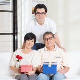 Pais superiores que recebem o presente da criança Foto de Stock