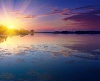 Paisagem agradável com por do sol no lago Imagem de Stock Royalty Free