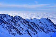 A paisagem alpina bonita com céu azul, luz do sol e mar nubla-se no inverno Montanhas de Fagaras Imagens de Stock Royalty Free