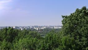 Paisagem através das árvores você pode ver a cidade nos bancos do rio Fotos de Stock