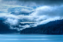 Paisagem azul do lago com nuvens nevoentas imagem de stock